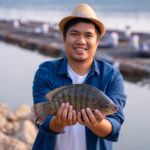 Fisherman holding big tilapia fish, freshwater fish that was raised in ponds and cages.